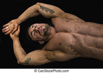 Attractive young muscle man laying on the floor