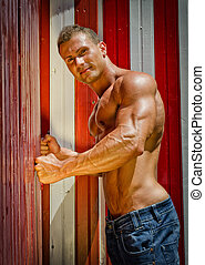 Attractive young muscle man leaning against colorful beach changing rooms
