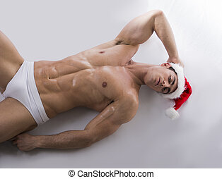 Attractive young muscle man on the floor in Santa Claus's red hat