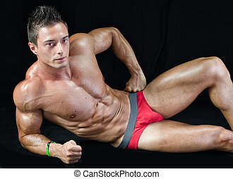 Attractive young muscle man on the floor with muscular ripped body