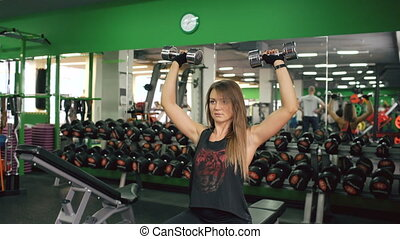 Attractive young muscular woman exercising in gym and working out with dumbbell