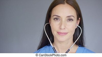 Attractive young nurse using a stethoscope