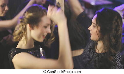 Attractive young people on dance floor at club throwing hands