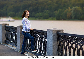 Attractive young pregnant woman relaxing in a park at a...