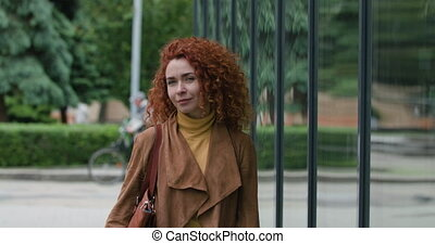 Attractive young red-haired curly woman with a bag on her shoulder walks near the glass wall looking at the camera