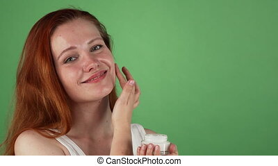 Attractive young red haired woman applying face cream -...
