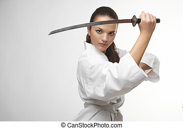Attractive young sexy women with samurai sword on white...