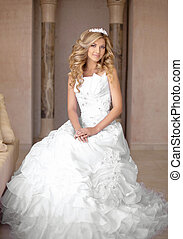 Attractive young smiling bride woman in wedding dress. Beautiful girl with curly hair style and professional bridal makeup posing in interior.
