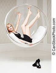 attractive young smiling woman lying in round chair