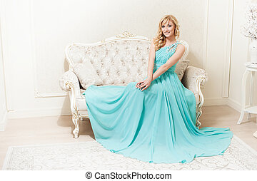 attractive young smiling woman sitting at sofa