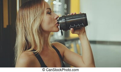Attractive young sport girl drinking water in a professional gym