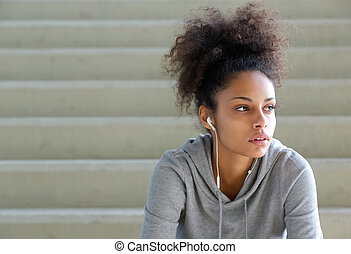 Attractive young sports woman sitting on steps with earphones