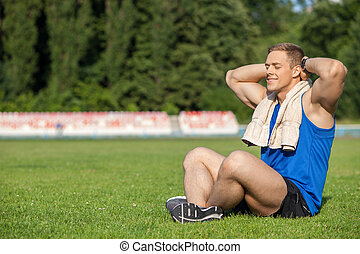 Attractive young sportsman is relaxing in stadium
