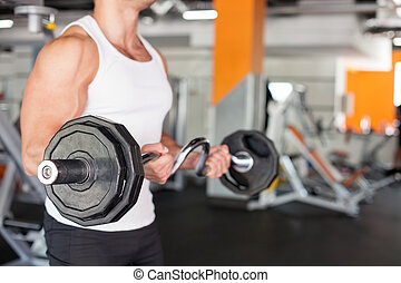 Attractive young sportsman is training in fitness center