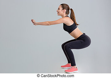 Attractive young sportswoman doing squats