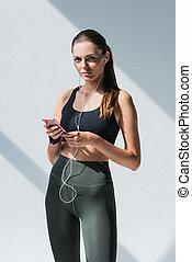 sportswoman in earphones using smartphone