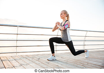 Attractive young sportswoman stretching legs on pier -...