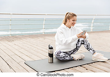 Attractive smiling young sportswoman wearing hoodie sitting on a fitness mat outdoors at the beach, using mobile phone while listening to music