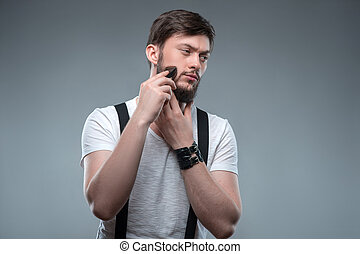 Attractive young strong man is shaving himself