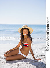 Attractive young tanned woman wearing straw hat posing