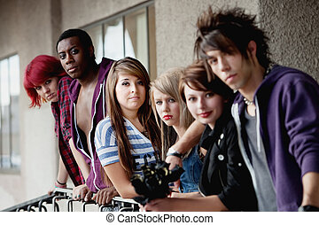 Attractive young teen punks look at the camera as it selectively focuses on the brunette in the middle.