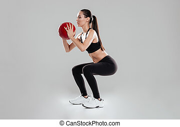 Attractive young woman athlete doing squats with medicine ball