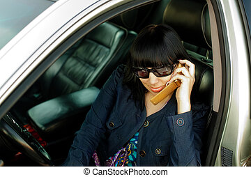 Attractive young woman calling by cellular phone in car