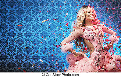 Attractive young woman celebrating among rose petals