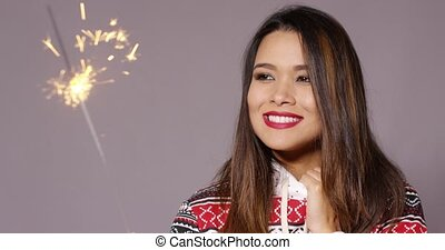 Attractive young woman celebrating with a sparkler -...