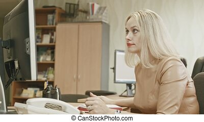 Attractive young woman - Charming office working answering the phone in her office in front of computer, slider shot