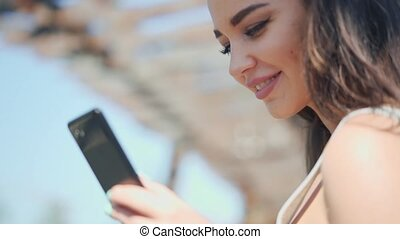 Attractive young woman chatting in a messenger with friends.