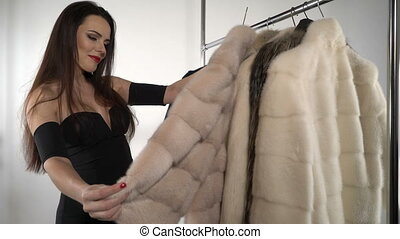 Attractive young woman chooses fur coats and jackets on hanger rack