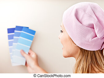 Attractive young woman choosing color for painting a room