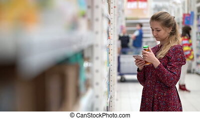 Attractive young woman choosing products in supermarket marketplace