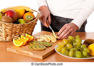 Attractive young woman cuting fruits and preparing fruit salad