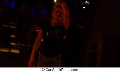 Attractive young woman dancing in a nightclub on a dancefloor