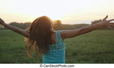 Attractive young woman dancing outdoors on a sunset with sun shining bright through the sun in slow motion.