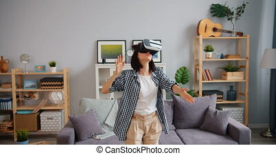 Attractive young woman is dancing relaxing in augmented reality glasses at home having fun moving arms touching head. Youth, gadgets and apartment concept.
