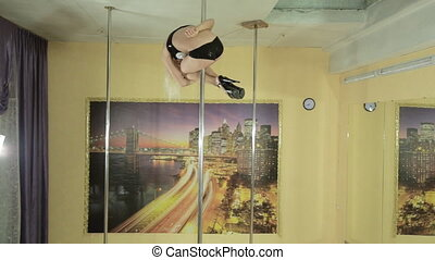 Attractive young woman doing acrobatic tricks on pole
