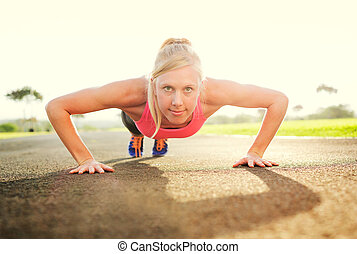 Attractive young woman doing push up, sunrise early morning...