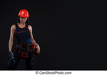Attractive young woman doing repairs at black background. Portrait of a female construction worker. Building, repair concept. Copy space