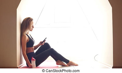 Attractive Young Woman Doing Yoga and Using Cell Phone Sitting on The Floor.