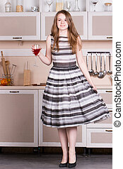 Attractive young woman dress holding a glass in her kitchen.
