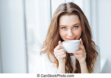 Attractive young woman drinking cofee at home