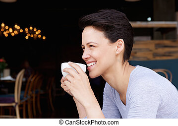 Attractive young woman drinking coffee at cafe