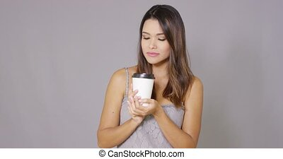 Attractive young woman drinking takeaway coffee