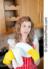 Attractive young woman drying dishes