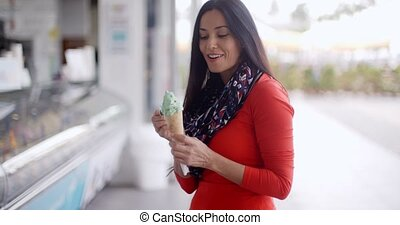 Attractive young woman eating an ice cream cone