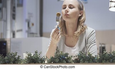 Attractive young woman eating lunch in cafe.