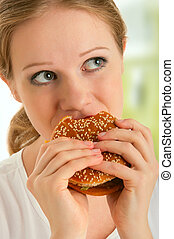 attractive young  woman eats unhealthy food, hamburger